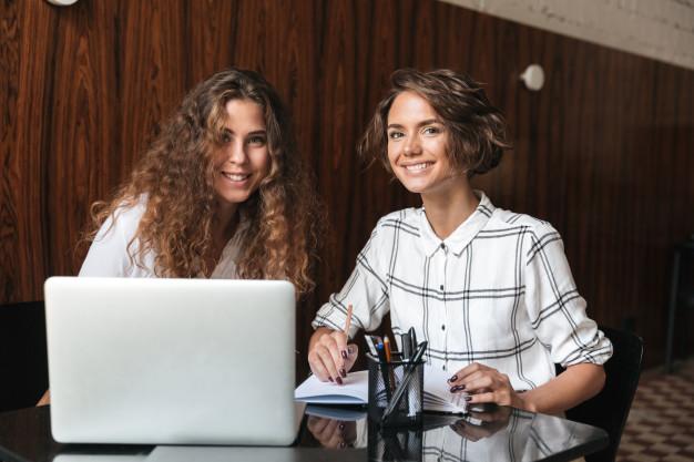 dos-mujeres-rizadas-sonrientes-trabajando-junto-mesa_171337-16615